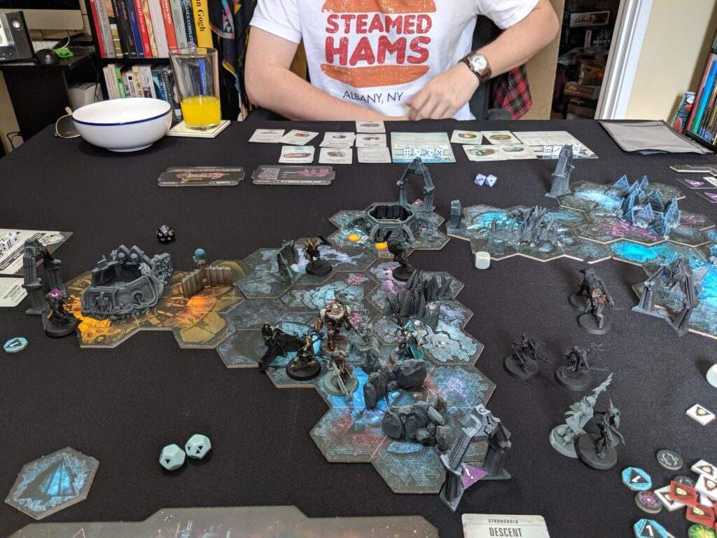 Blackstone Fortress game laid out on black table. Man in a Steamed Hams t-shirt in background.