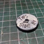 A magnet key on a cutting mat. The top of the round metal reads 'This side in' in handwriting