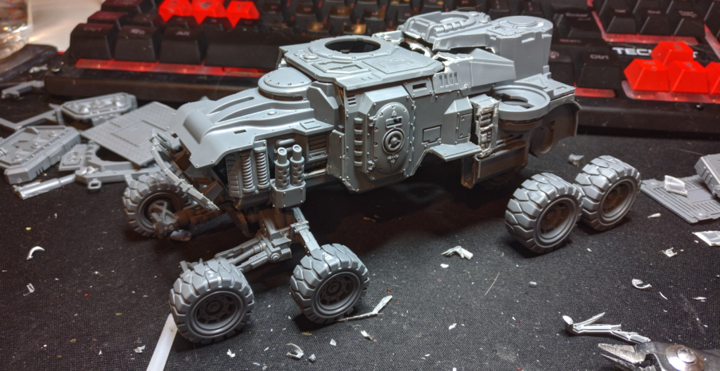 A large unfinsihed vehicle with tiny wheels, assembled from multiple kits.