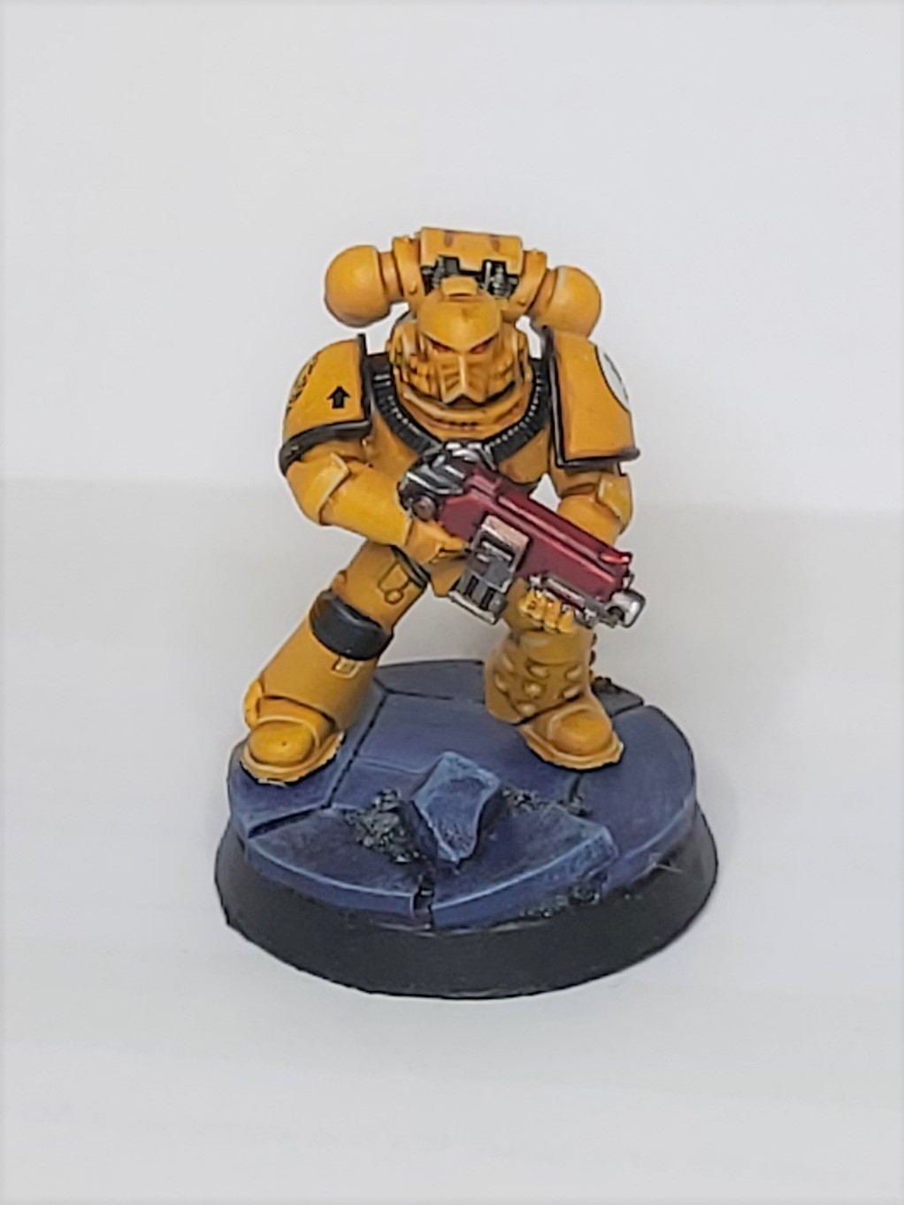 Model imperial fist, a space marine painted yellow and mounted on a sculpted base of blue rubble