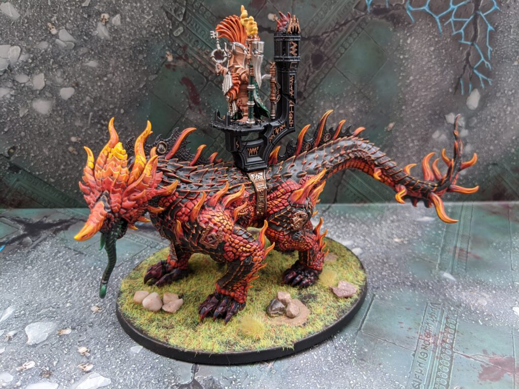 A magmadroth model, painted in a fiery red and black colour scheme on a grassy base.
