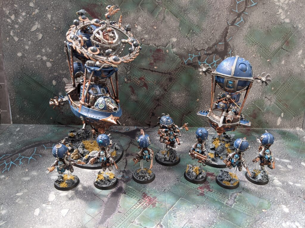 Some Kharadron Overlords models. There are two airships accompanied by some endrinriggers, all painted in a blue, silver and gold colour scheme with rocky bases. One of the airships has been converted into a Celestial Hurricanum by adding on orrery to it.