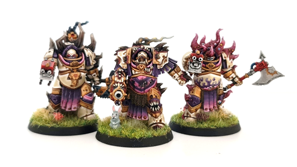 A photo showing the three completed models of the Tainted Cohort. They are painted with pale armour, pink and purple accents and gold trim. Their weapons are accented with red casings. They are mounted on grassy bases with additional flower tufts. A grey rabbit is visible on one base.