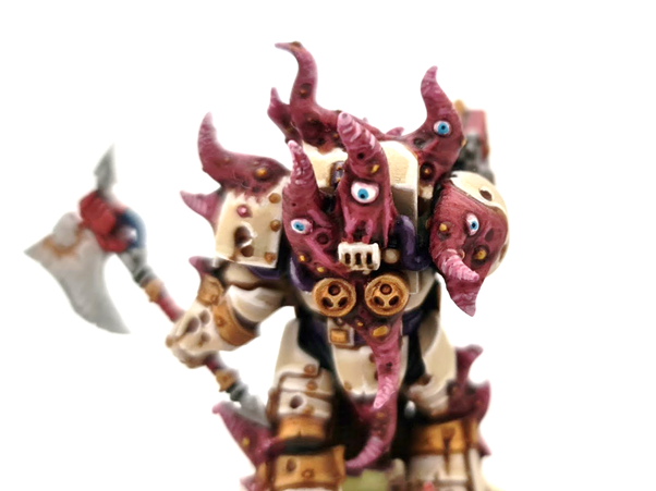A photo showing pink tentacles with several blue eyes poking through armour plating on a chaos terminator.