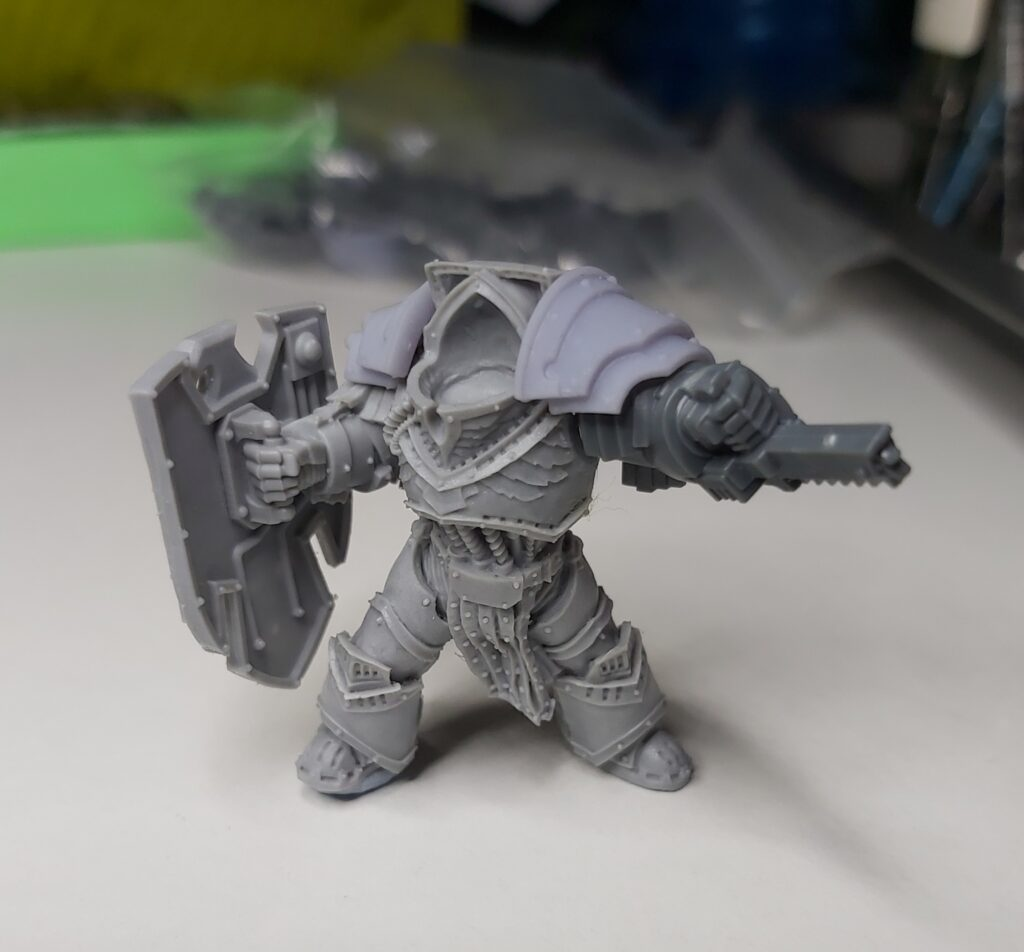 A single space marine special character with a heavy shield and chainfist. he is unpainted and partially assembled: his head is missing.