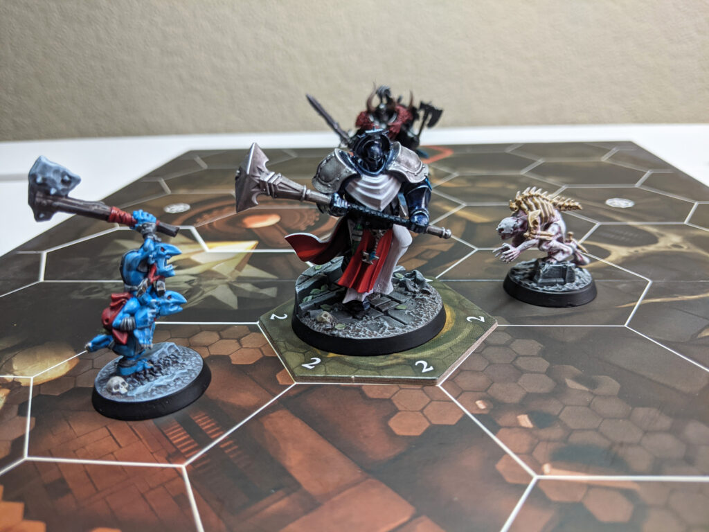 A close-up of some Underworlds fighters during a game of Arena Mortis. A Stormcast Eternal is in the centre, with a Gnoblar on his left, and a Ghoul on his right.