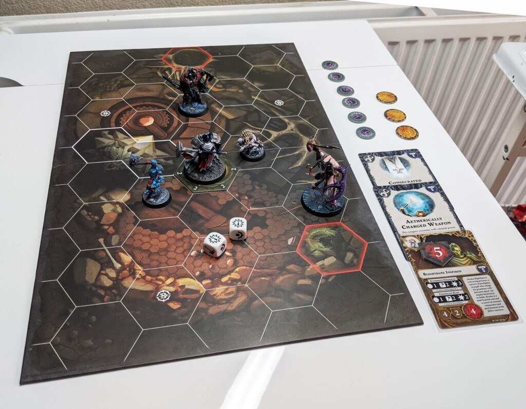 A Warhammer Underworlds game board with five fighters on it. There is a Stormcast Eternal in the middle surrounded by a Ghoul and a Gnoblar, with a Chaos Warrior and a Slaangor looking on. Tokens and cards are laid out on the right hand side of the board. There are two dice, both showing critical successes.