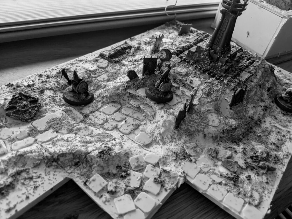 A black-and-white image of a terrain board, on a large squared base.