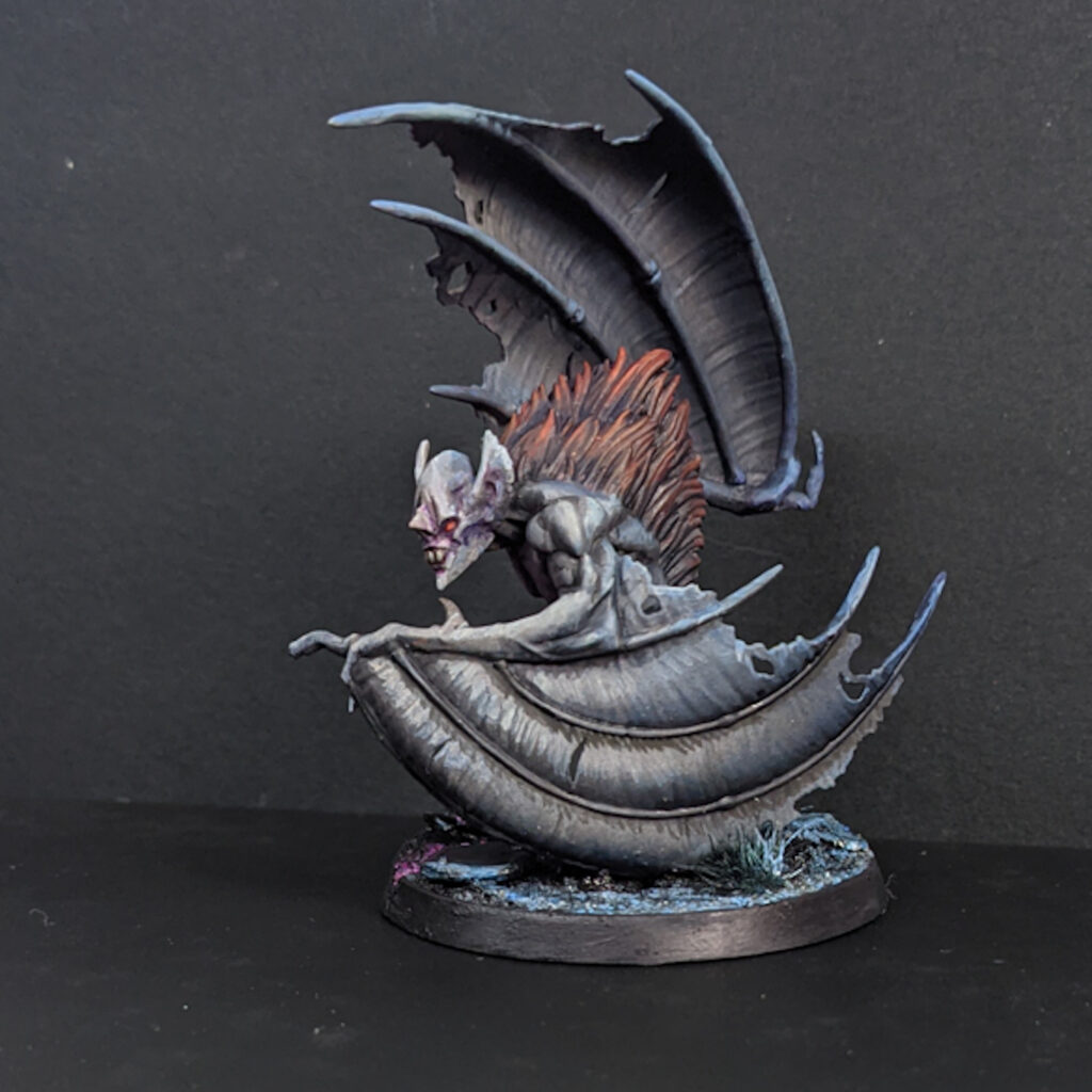 A model of a bestial bat-winged creature, painted in a cold blue-grey with a tuft of russet fur on its back.