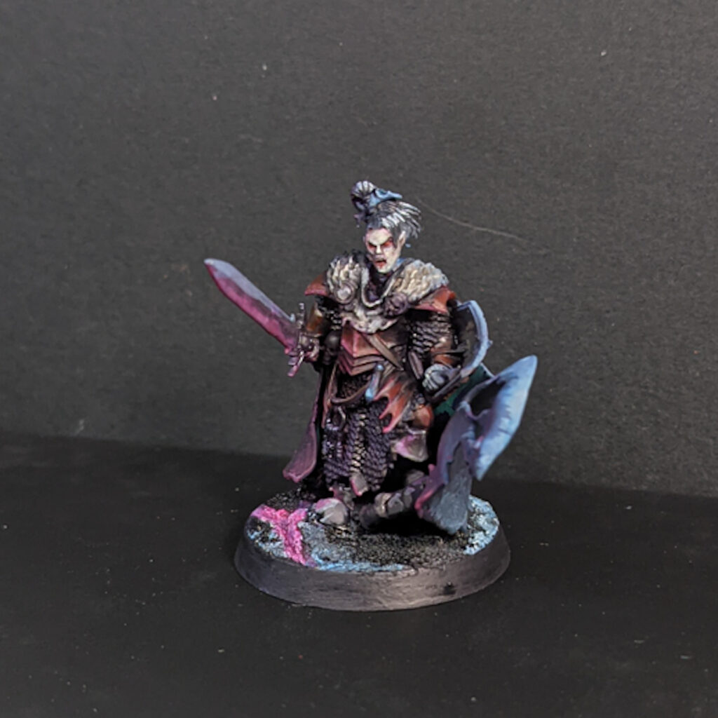 A model vampire in archaic ornate armour, painted in cold red and blue.