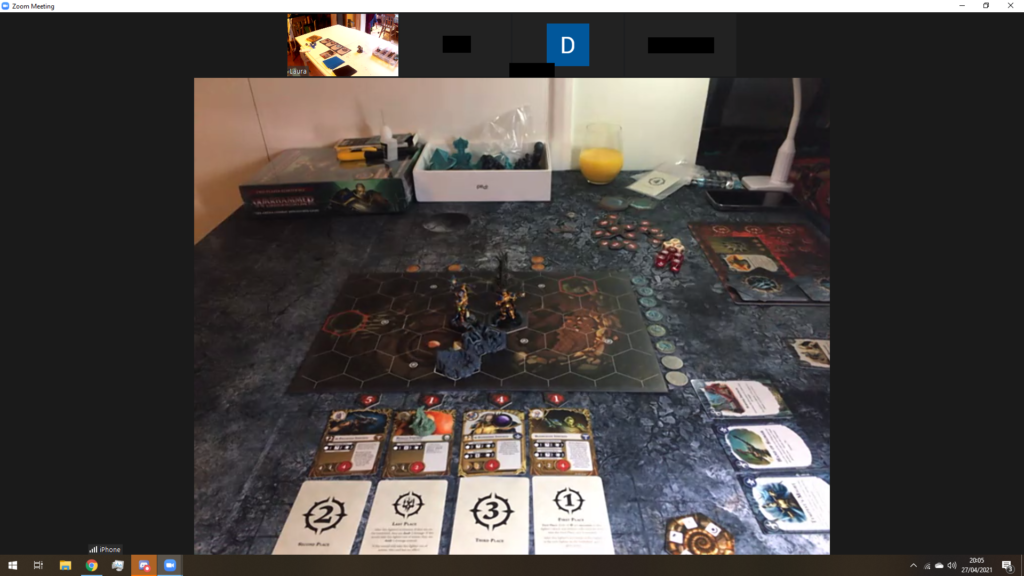 A screenshot of a Zoom meeting. The main camera feed shows a game of Arena Mortis in progress.
