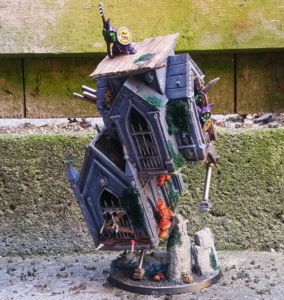 a 28mm kitbash that represents two walking houses with goblins holding on