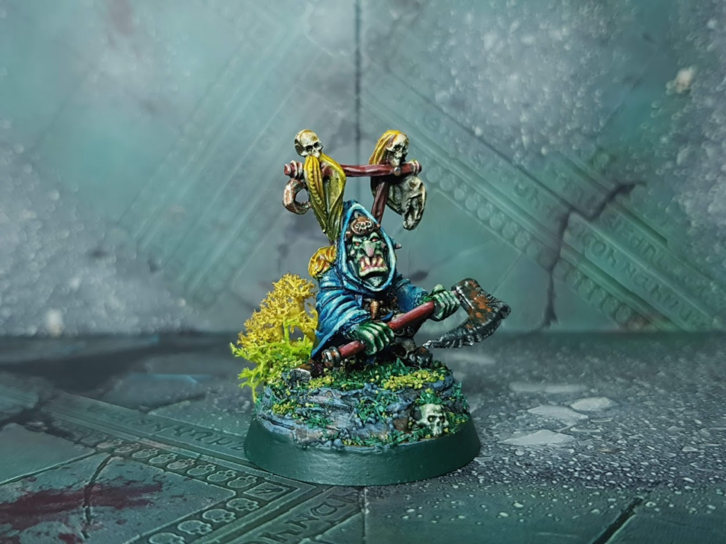 a 28mm goblin boss in blue robes and holding an axe