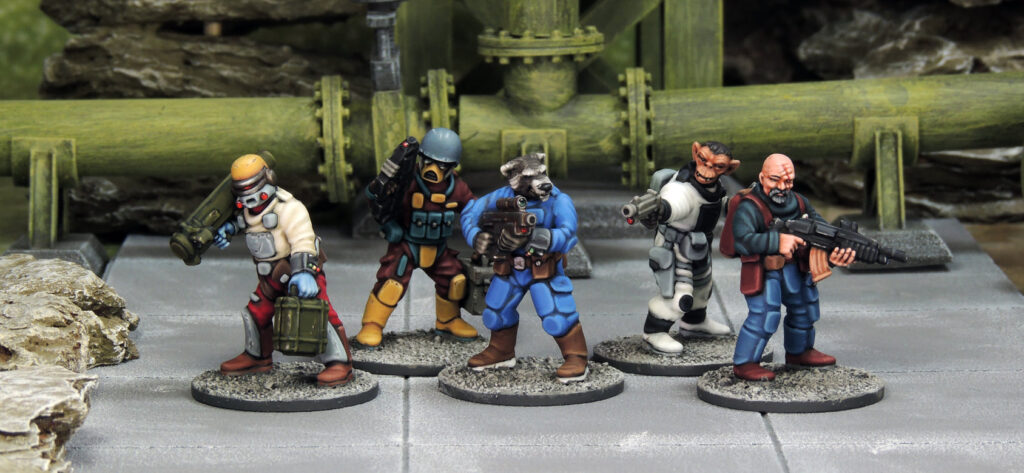 five 28mm Stargrave miniatures in a range of poses. one holds a missile launcher, one a pistol, one is a raccoon headed humanoid, one an ape and the last is a bald white man with an assault rilfle