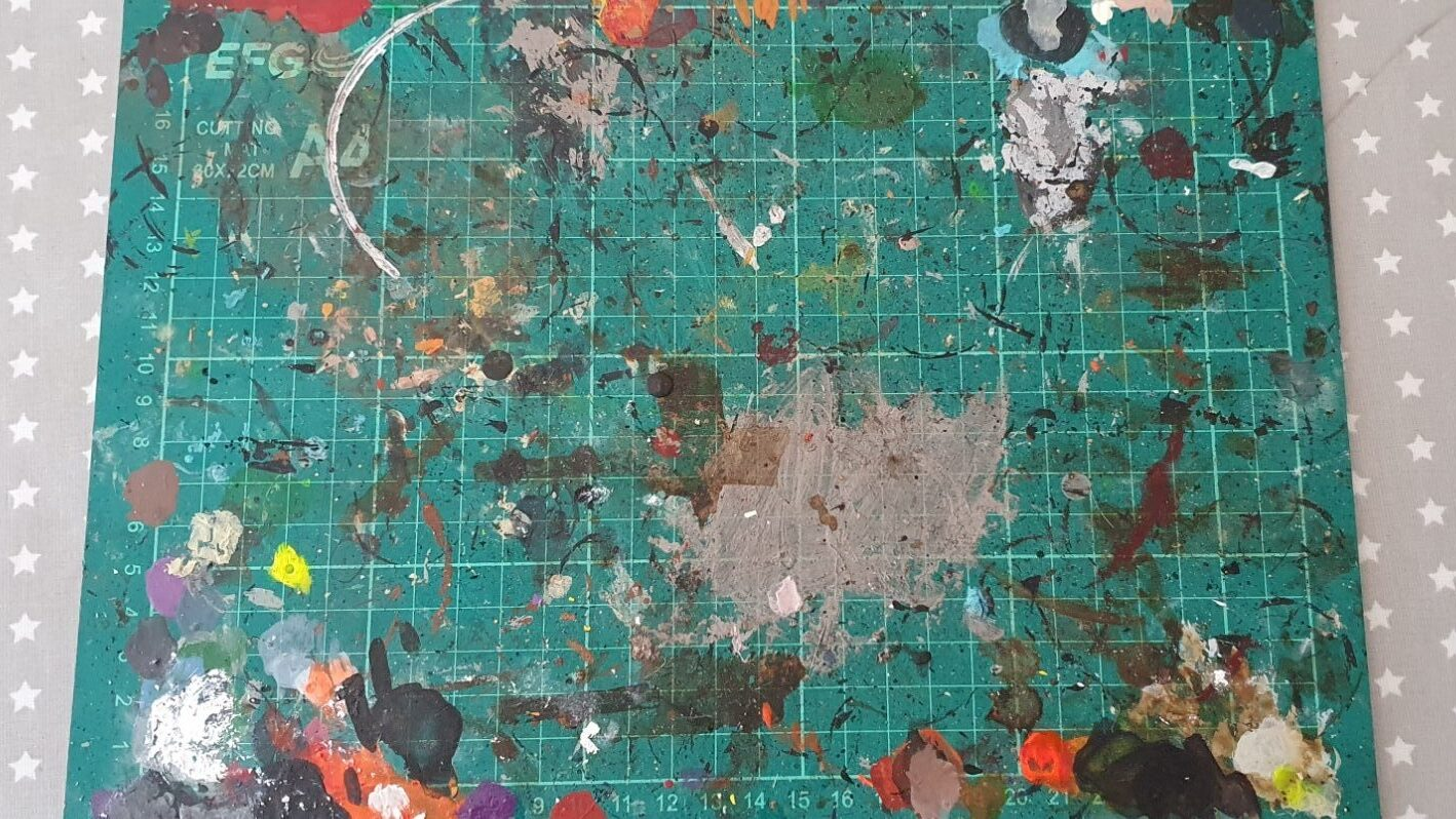 A paint covered cutting mat