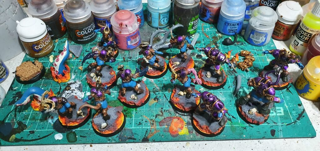 a cutting mat with a number of models and citadel paint pots covering the surface