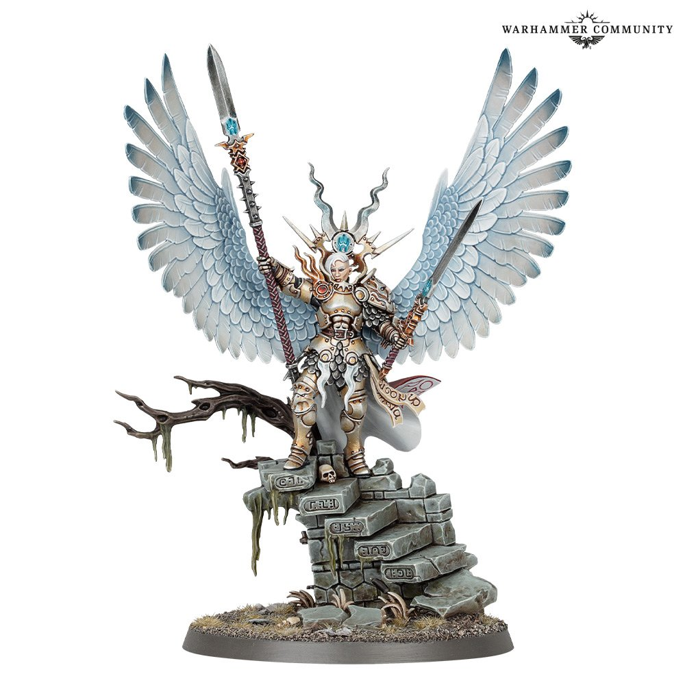 A model woman in pale gold armour, standing on a ruined staircase. She carries a spear and sword, and has two huge white feathered wings.