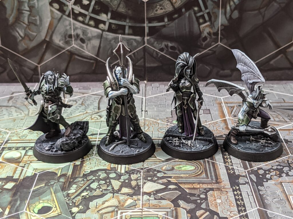 Four vampire models, painted with green armour, pale skin, and purple robes.
