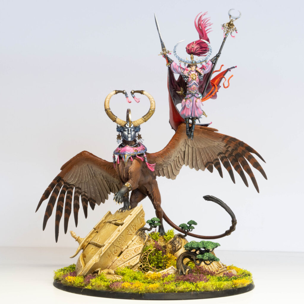 A painted model of an elf and its flying mount. The elf is painted pink, and the mount is brown.