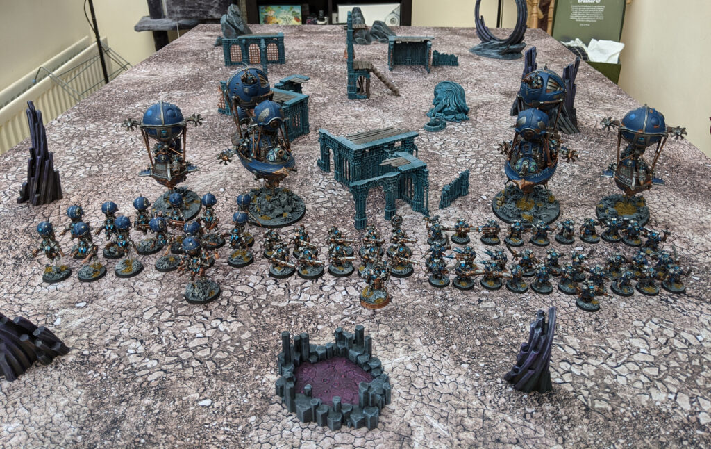 A Kharadron Overlords army, painted in a blue colour scheme, laid out on a gaming table.