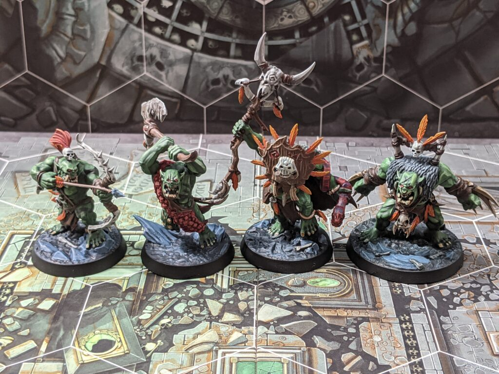 Four orc models, painted with green skin and ornamented with orange feathers.