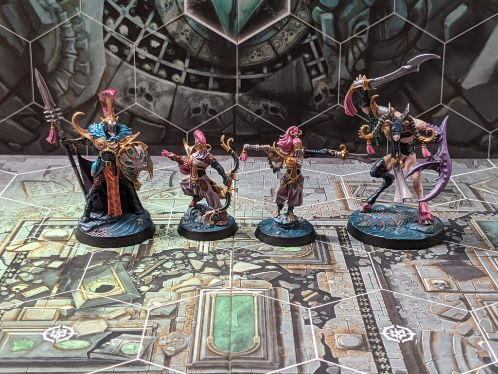 An Underworlds warband consisting of two small humans, one large human, and a goat beastman with a large claw. They are painted in a pink and gold colour scheme.
