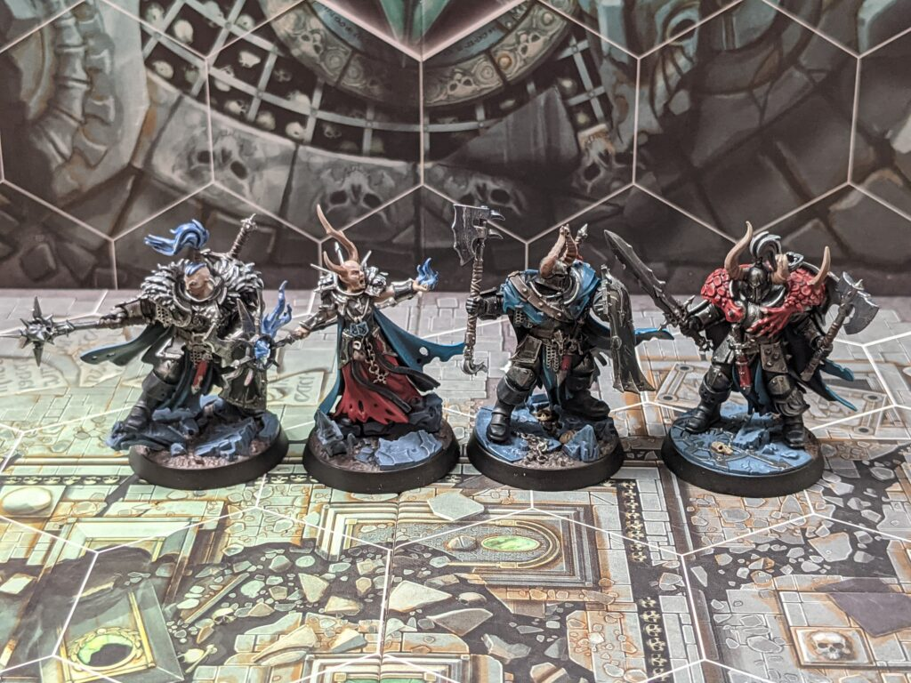 Four chaos warrior models, painted with shiny black armour, and blue cloaks.