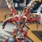 Skarbrand, sat fully painted in red, bone and brass on a desk