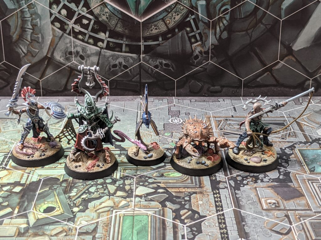 An Underworlds warband consisting of five models: three elves, a fish, and a crab.