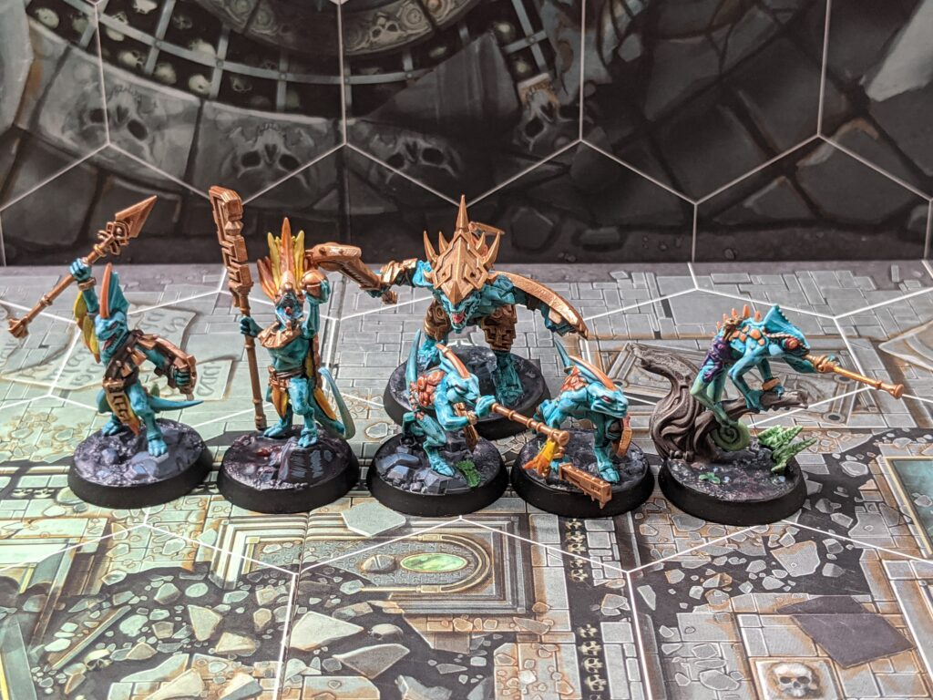 Six lizardmen models, painted in an orange and blue colour scheme, with gold weapons.