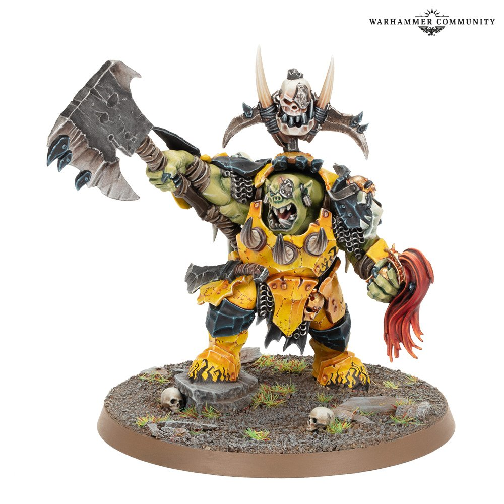 A model of an ork leader, dressed in crude yellow armour and carrying a massive cleaver.