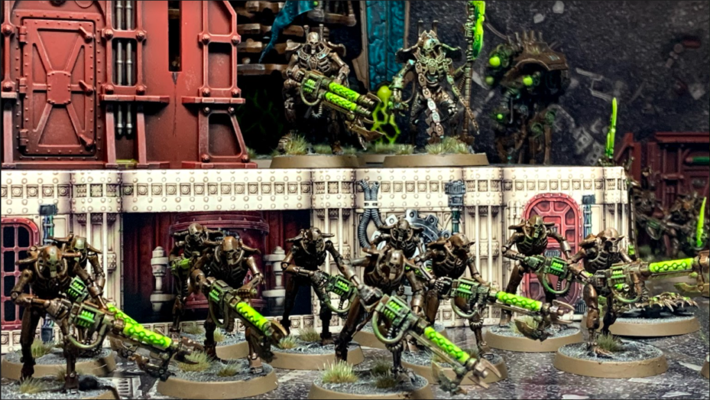 A group of Necron Warriors march in front of a building, overseen by a Royal Warden and an Overlord. The Warden carries a large double-barrelled gun which glows green, whilst the Overlord has a glowing green halberd.