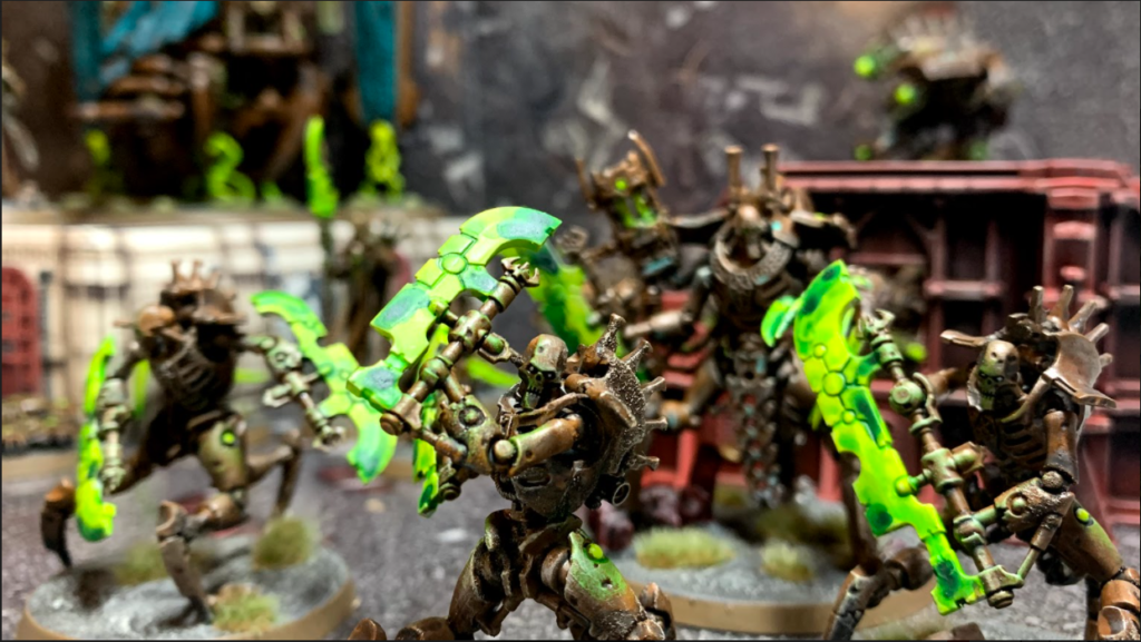 The Skorpekh Lord watches from the background as three skorpekh destroyers, smaller versions of the tripedal robot armed with blades, advance on the camera.