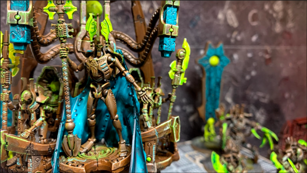 The Silent King, a tall robotic humanoid construct of dirty metal, with a glowing green headdress and vibrant blue robes, stands atop a floating podium.