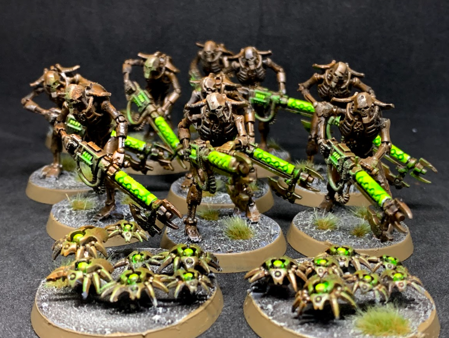 A group of dirty metal Necron Warriors, the foot troops of the faction. They hold glowing green guns, and are accompanied by small robotic scarabs in the same colours.