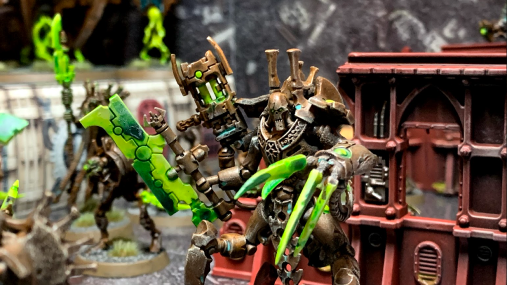 The Skorpekh Lord, a three-legged, three-armed large robotic construct with a claw, a blade and a gun. Painted in dirty metals, with glowing green weapons.