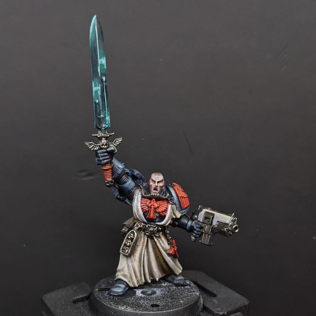 A black-armoured space marine in cream robes, holding aloft a power sword