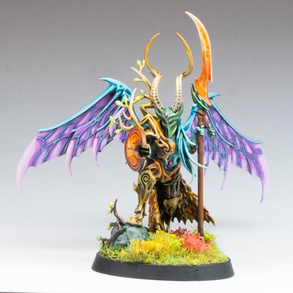 a brightly painted dryad/spirit with wings, a spear and shield