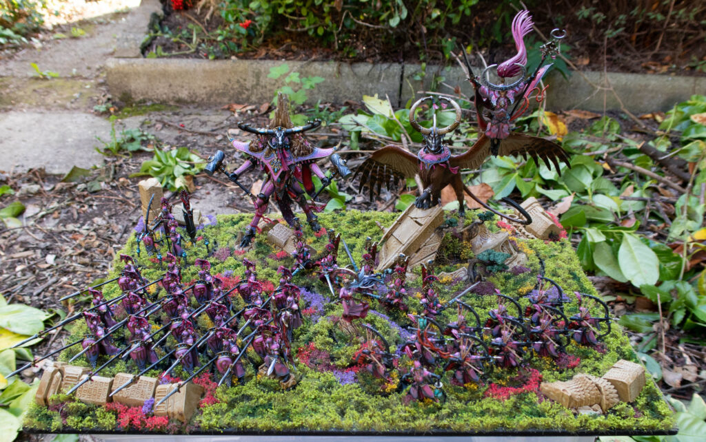 A pink army of elves, on a grassy display board, set outside in a leafy garden