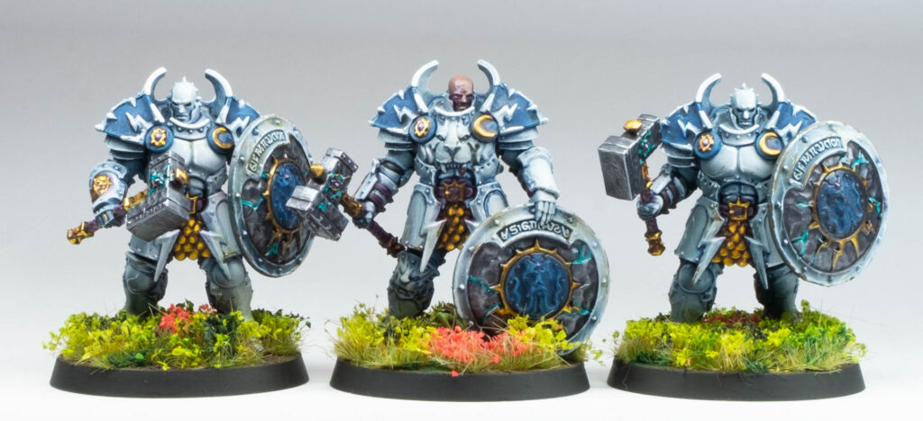 Three heavily armoured stormcast troops, in a white and blue scheme on green fields