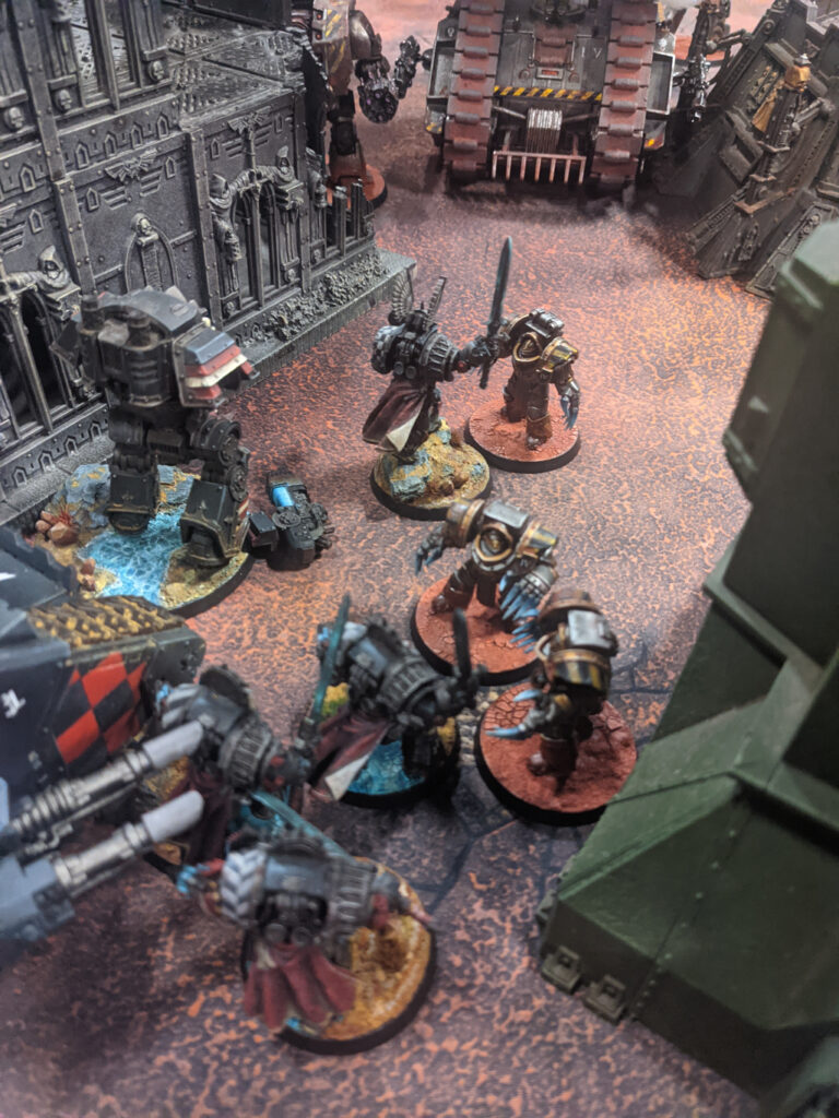 Units from the dark angels (black) and the iron warriors (metal with hazard stripes) clash on the tabletop