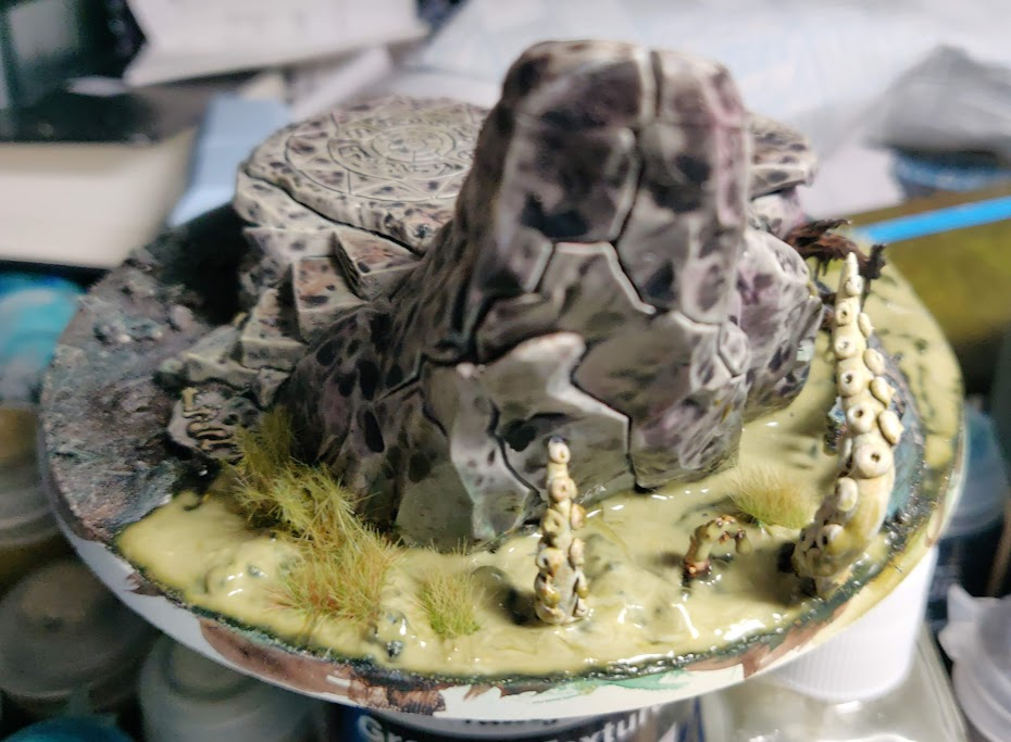 a pool of green gel drying around a rock on a large base